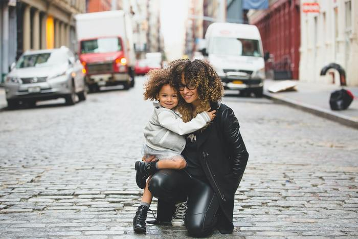 Mothers Day photo of a mom and her daughter hugging in the street